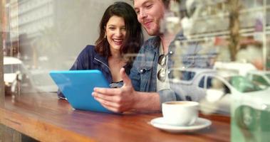 Frau und Mann sitzen im Café mit Tablette video