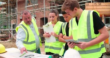 constructeur sur chantier discutant du travail avec les apprentis