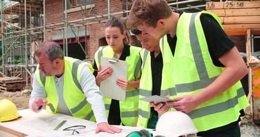 Constructor en sitio de construcción discutiendo el trabajo con aprendices
