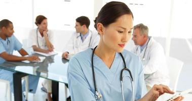 enfermera feliz mirando a la cámara con el personal detrás de ella