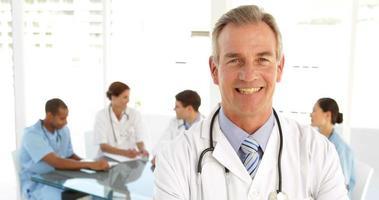 Arzt schaut in die Kamera und sein Personal hinter ihm video