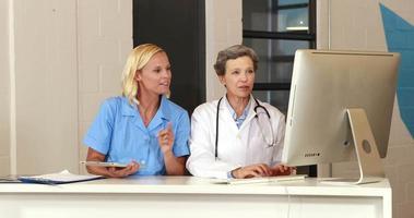 doctoras usando tableta y computadora