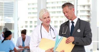 dois médicos olhando para a câmera com seus colegas atrás