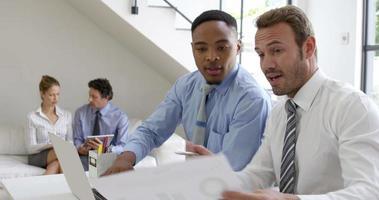 chiudere su due uomini d'affari sorridendo e lavorando con un laptop