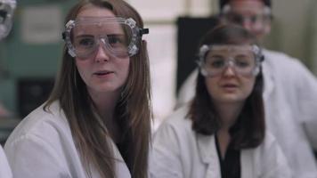 gli studenti in un laboratorio di scienze fanno domande ai loro professori