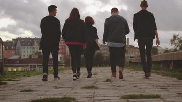 grupo de cinco adolescentes felizes, caminhando para a frente para fora da câmera em ambiente urbano. video