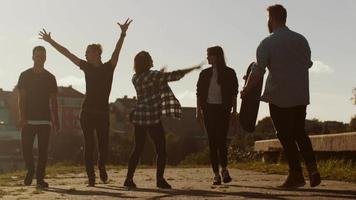 Gruppe von glücklichen Teenagern, die lachen, Hände heben, springen, während sie sich in Richtung Kamera bewegen. video