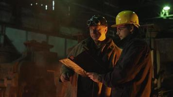 ingegnere e operaio conversano in fonderia. ambiente industriale grezzo. colpo centrale.