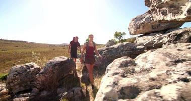 casal em forma caminhando com mochilas explorando a natureza