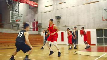 giocatori di basket che passano la palla lungo il campo durante una partita e fanno un canestro