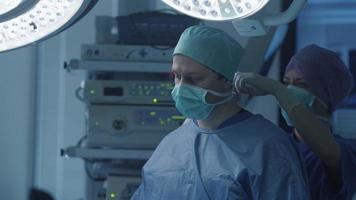 enfermera ayudando a poner la mascarilla quirúrgica al doctor. video