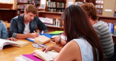 alunos trabalhando juntos na biblioteca com uma garota sorrindo