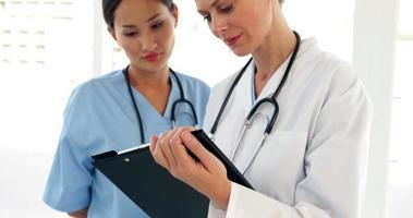 médicos mirando un archivo y mirando a la cámara