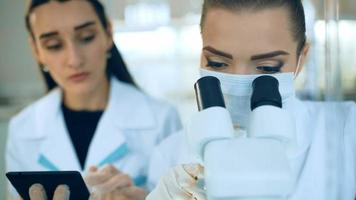 Femme scientifique regardant à travers un microscope en laboratoire