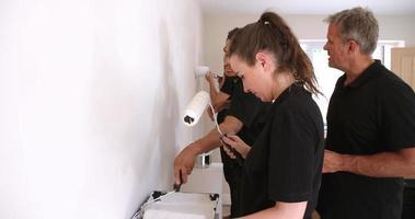 decoratore che consiglia il team che dipinge un muro interno