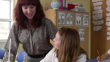 la maestra ayuda a la alumna con el trabajo en clase filmada en r3d