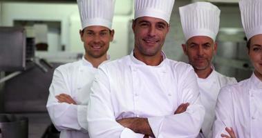 quatre chefs heureux regardant la caméra avec les bras croisés