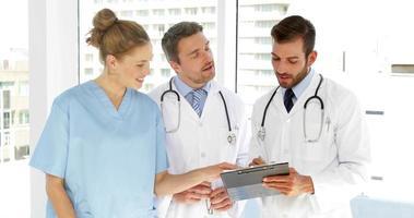 Equipo médico discutiendo el papeleo en el portapapeles