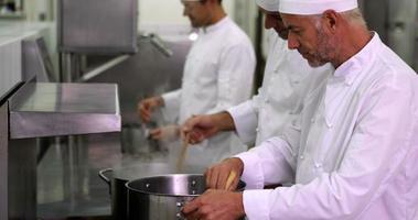 chef cuisinier en remuant une grande casserole à la cuisinière video