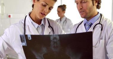 Ärzte, die Röntgen auf der Station studieren video