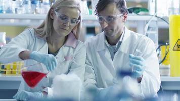 deux scientifiques ajoutent du liquide à de l'azote froid dans un laboratoire.