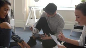 grupo de alunos senta no chão e colabora no projeto video