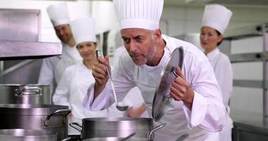 chef principal degustando panela de sopa e fazendo sinal de ok