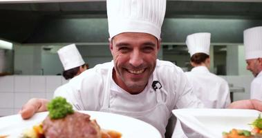 Chef feliz mostrando dos platos a la cámara