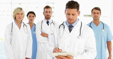 médico serio escribiendo en el portapapeles mientras el personal está de pie