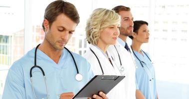 ernsthafter Chirurg, der in die Zwischenablage schreibt, während das Personal steht