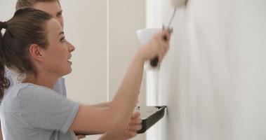 Pareja joven decorar la casa con rodillos para pintar, cerrar