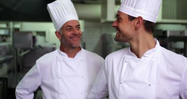 Dos chefs sonrientes dando pulgares a la cámara