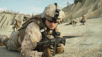 Trupp voll ausgestatteter und bewaffneter Soldaten, die während einer Militäroperation in der Wüste kriechen. Zeitlupe.