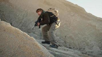 bewaffneter Terrorist, der in der Wüstenumgebung geht