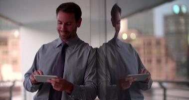 empresário usando telefone inteligente na varanda e apreciando o pôr do sol video