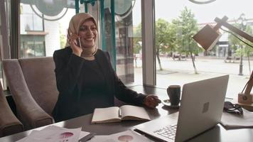 Smiling Arab businesswoman talking on phone in cafe