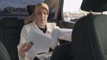 imprenditrice araba che lavora nel sedile posteriore della macchina