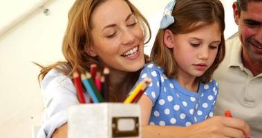 genitori felici e figlia che colorano insieme