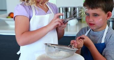 glückliche Geschwister, die zusammen einen Kuchen machen