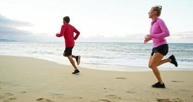Paar zusammen am Strand joggen