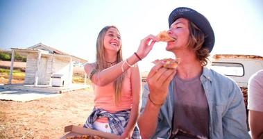 amici seduti fuori insieme a mangiare pizza da asporto