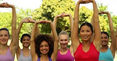 lezione di fitness che allunga le braccia insieme