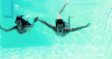coppia felice che salta in piscina insieme