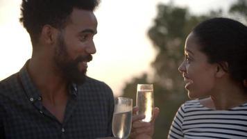 coppia godendo un bicchiere di champagne all'aperto insieme