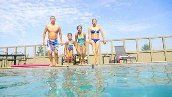 Hispanic family jumps into a pool together