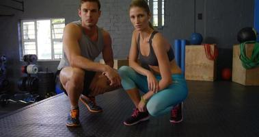 Man and woman posing together in gym video