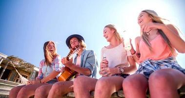 amigos sentados juntos bebiendo alcopops y riendo