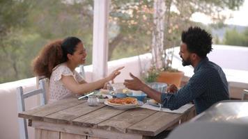 casal desfrutando de uma refeição ao ar livre no terraço video