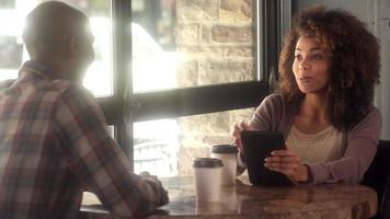 amici che utilizzano la tecnologia insieme in un caffè