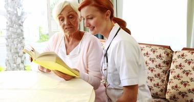 Krankenschwester und alte Frau lesen zusammen Buch